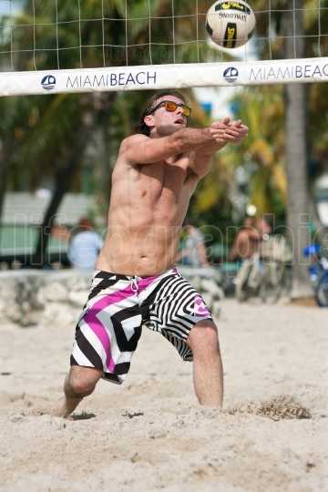 Man Uses Arms To Pass Ball In Beach Volleyball Game