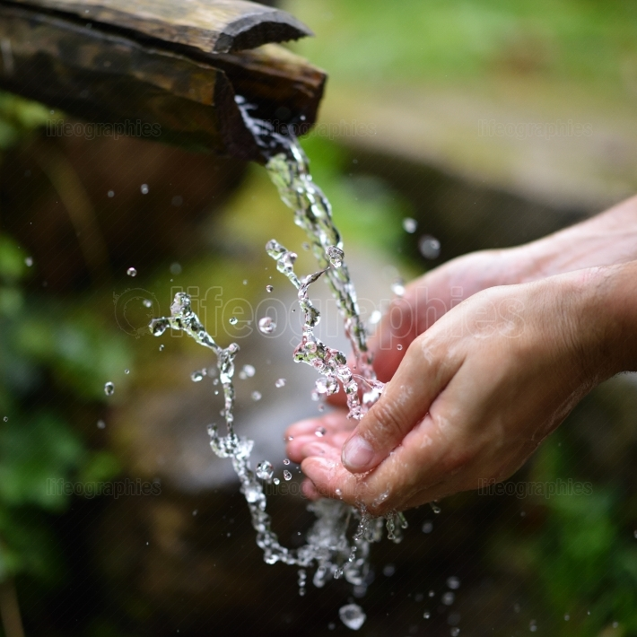 Man washing hands in fresh, cold, potable water of mountain spri