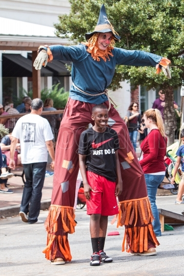 Man Wearing Scarecrow Costume On Stilts Poses For Photo