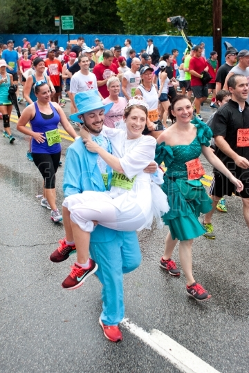 Man wearing tux carries fiancee across 10k race finish line