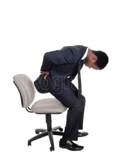 Man with back pain getting up from chair