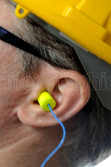 Man with protective ear plugs