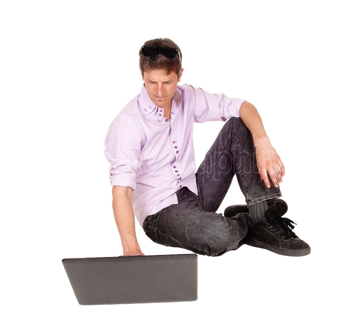 Man working on laptop of floor.