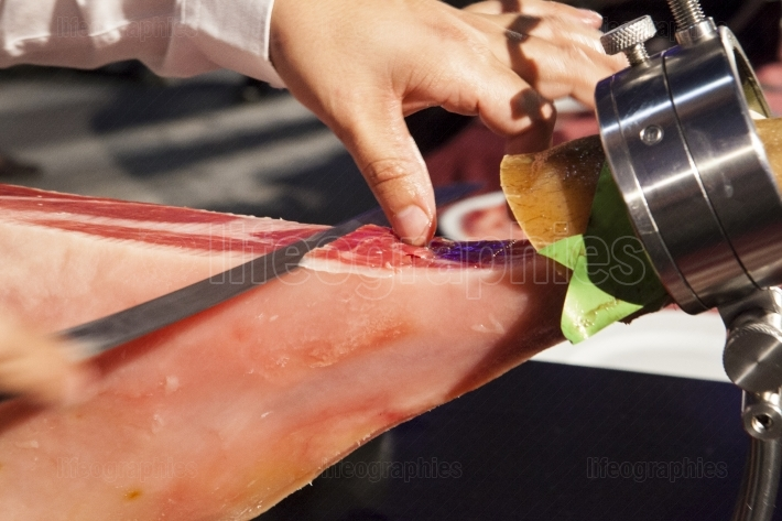 Master slicer holds the slice of iberian cured ham