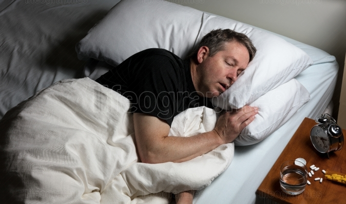 Mature man attempting to fall asleep after taking medicine