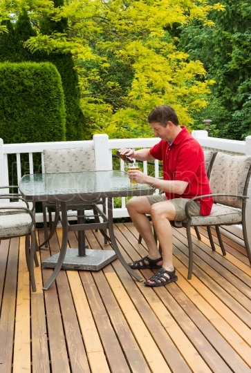 Mature man drinking at table on outside open patio