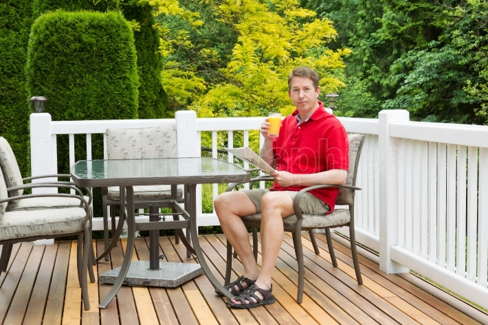 Mature man enjoying a fresh glass of juice while outside on pati