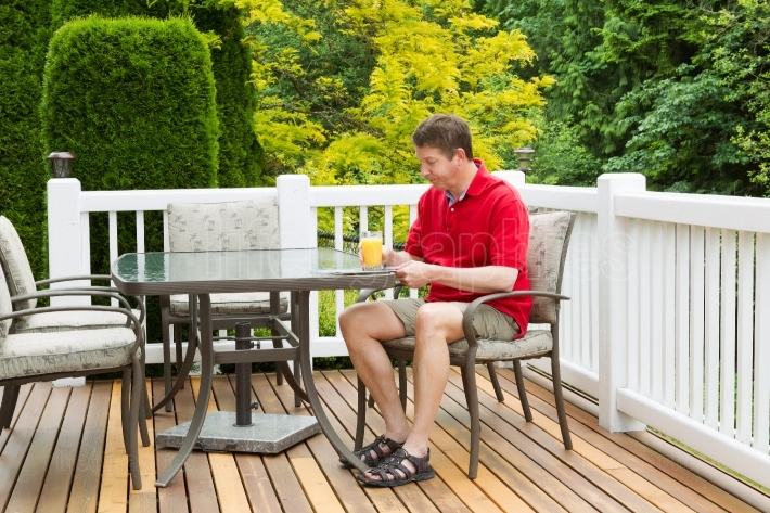 Mature Man enjoying orange juice while preparing to read outdoor