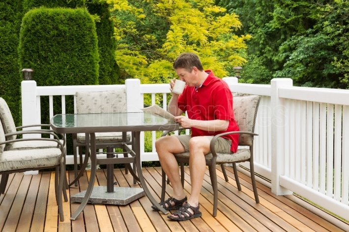 Mature Man Enoying Morning Coffee on Outdoor Patio in Morning
