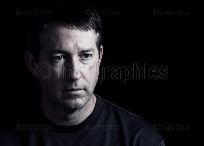 Mature man expressing negative emotions on dark background