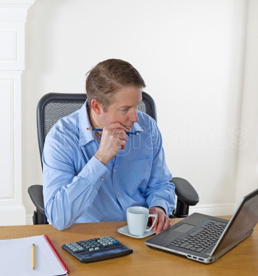 Mature man focused on laptop screen while working