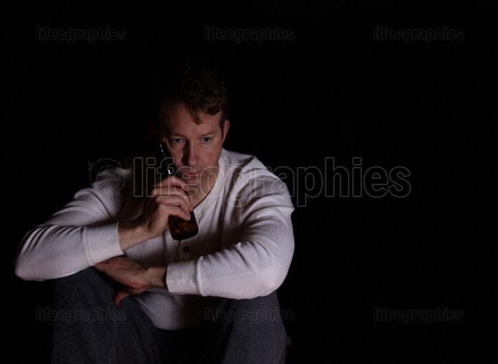 Mature man in thought while drinking beer in dark background