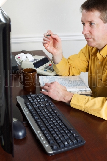 Mature man looking over numbers while working on taxes