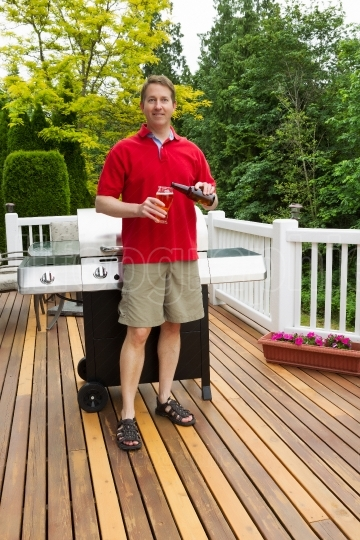 Mature man pouring beer into glass while outdoors on open patio