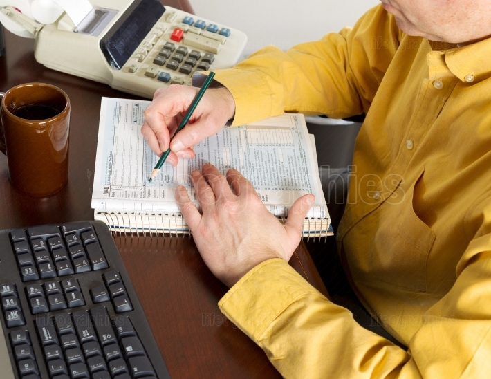 Mature Man putting information in tax tables