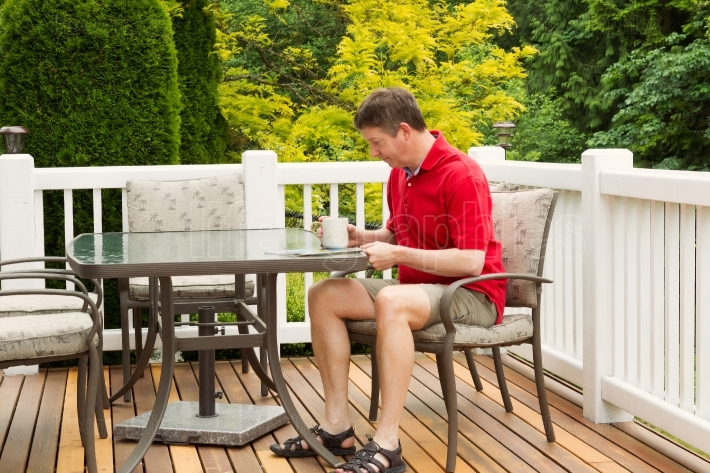 Mature Man reading outside on patio