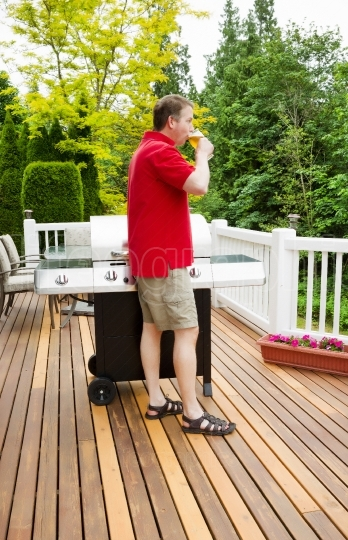 Mature Man relaxing by drinking beer on outdoor patio