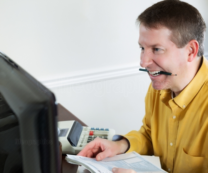 Mature man showing stress while doing Taxes