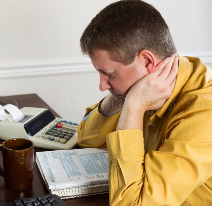 Mature man showing stress while working on his income taxes