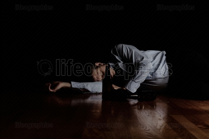 Mature man sleeping on floor after drinking too much with dark b