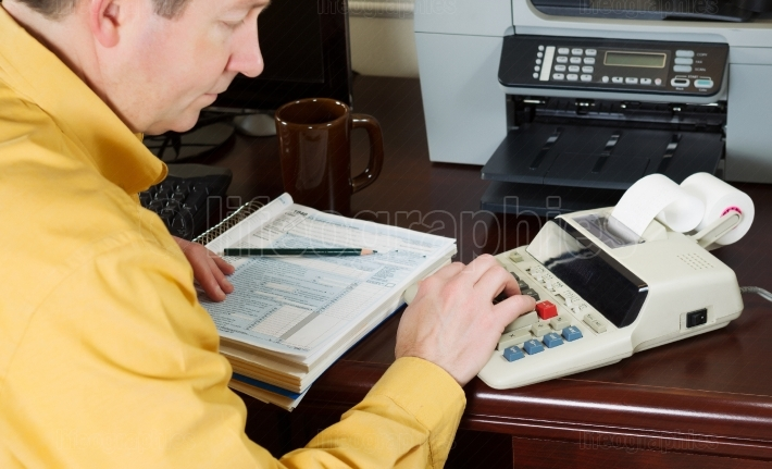 Mature man working the numbers on his income taxes