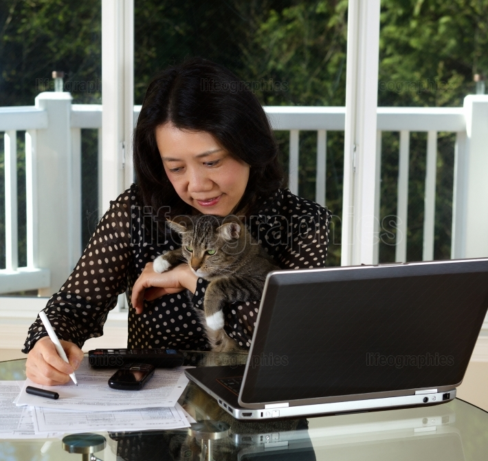 Mature woman and her pet cat working at home