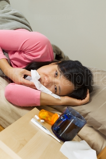 Mature woman Cleaning her nose with Tissue while lying in bed