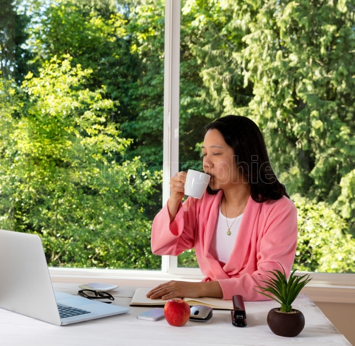 Mature woman enjoying her coffee in the morning while working fr