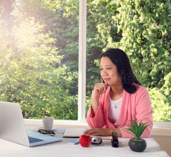 Mature woman enjoying morning light while working from home