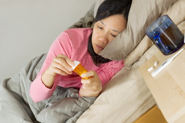 Mature Woman looking at Medicine Container while lying in bed
