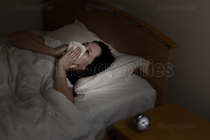 Mature woman sick while lying in bed at night time