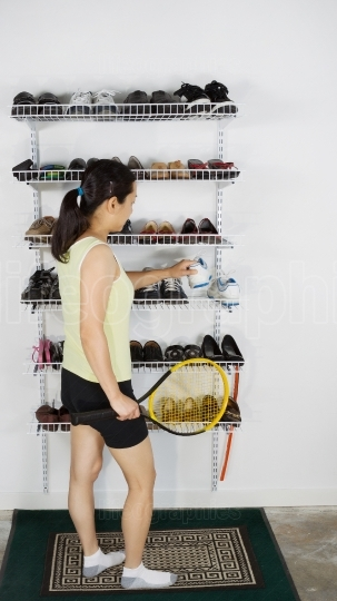Mature Woman taking shoes off rack for tennis session
