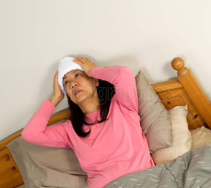 Mature woman treating Fever while in bed