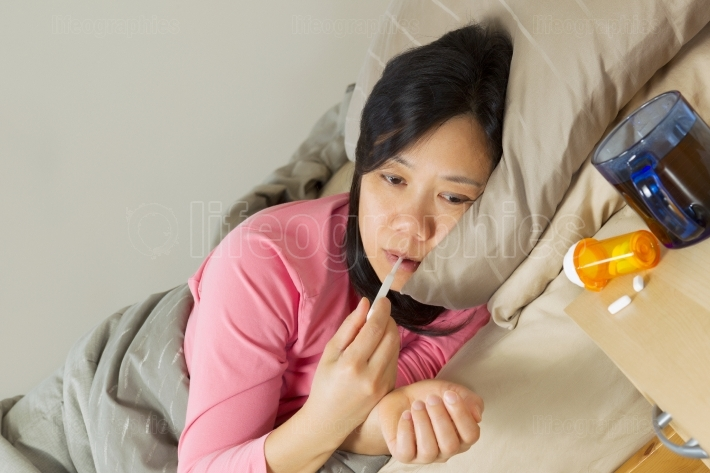 Mature Woman using Thermometer while lying in bed sick