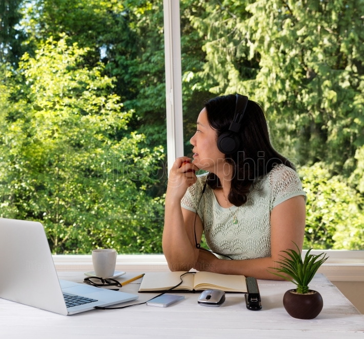 Mature woman working at home while looking out daylight window