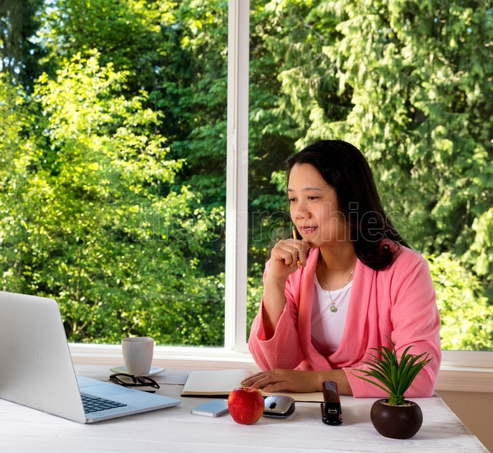 Mature woman working from home in morning attire with bright day