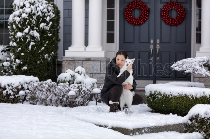 Mature women and her family dog outside in the snow