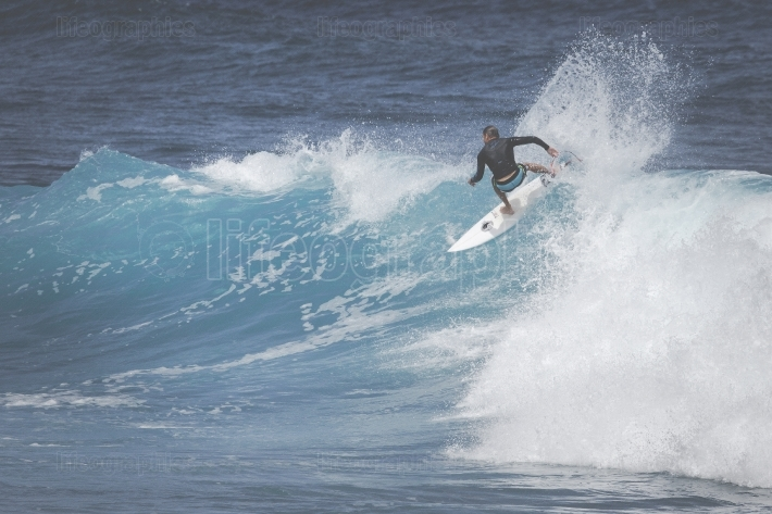 MAUI, HI - MARCH 10, 2015: Professional surfer rides a giant wav