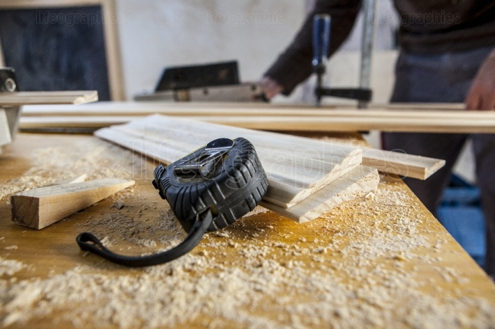 Measuring tape, wedge and wood pieces over sawdust