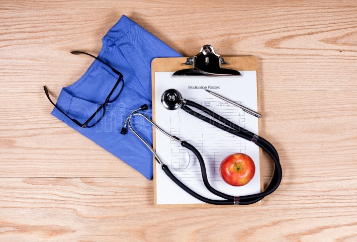 Medical clothing and equipment on wooden desktop