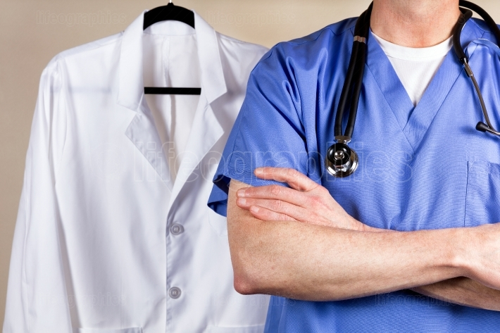 Medical doctor wearing blue scrubs with white consultation coat