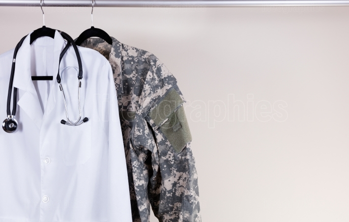 Medical white consultation coat and military uniform on hanger