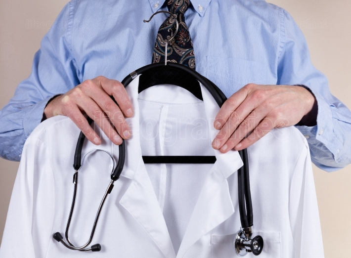 Medical white consultation coat with stethoscope being held by d