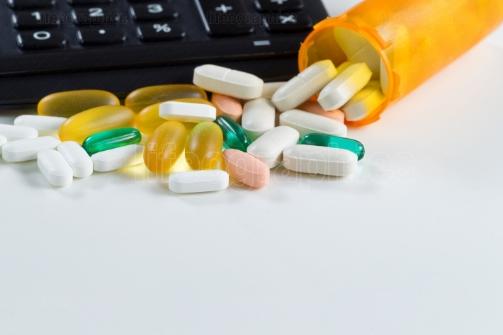 Medication pills with open bottle in front of calculator on whit