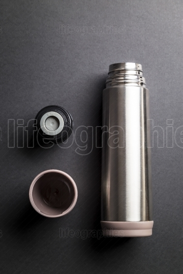 Metallic thermos over black background presentation
