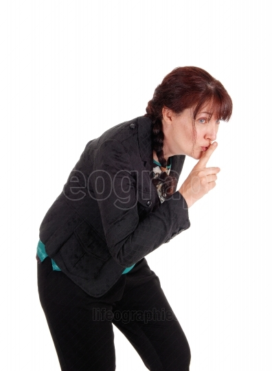 Middle age woman with finger over mouth.