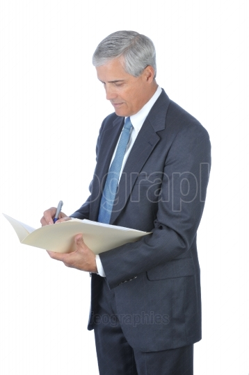 Middle Aged Businessman Writing in File Folder