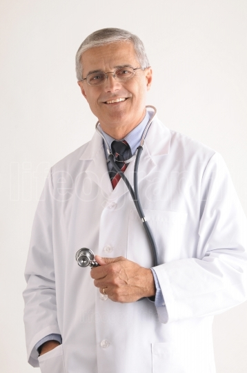 Middle aged doctor holding stethoscope