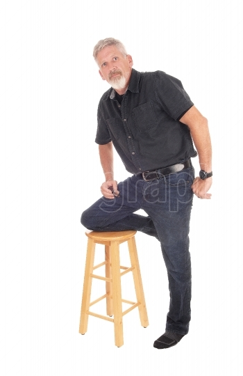 Middle aged man kneeling on chair