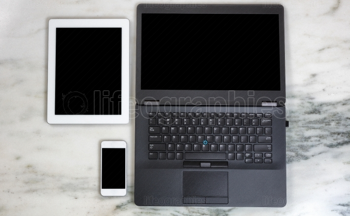 Modern mobile communication devices and computer on marble deskt